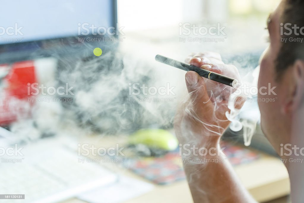Man smoking E-Cigarette at the office royalty-free stock photo