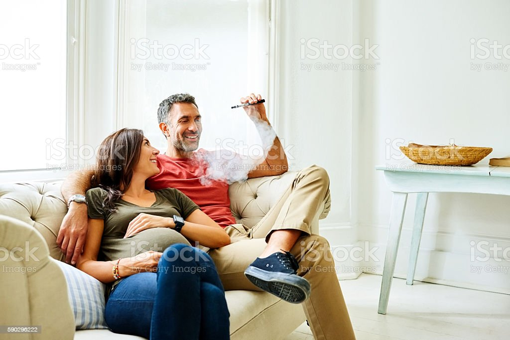Man smoking electric cigarette with pregnant wife on sofa stock photo