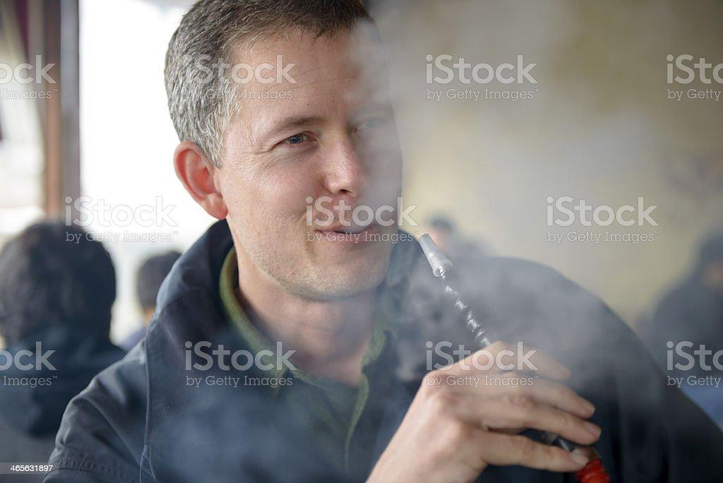 Man smoking hookah or water pipe in cafe stock photo