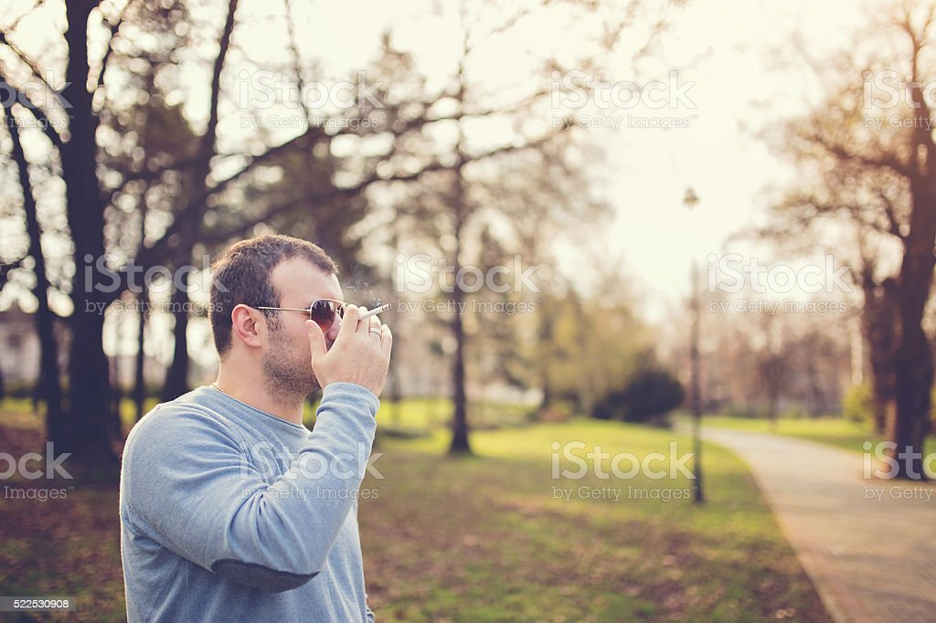 Man smoking in park stock photo