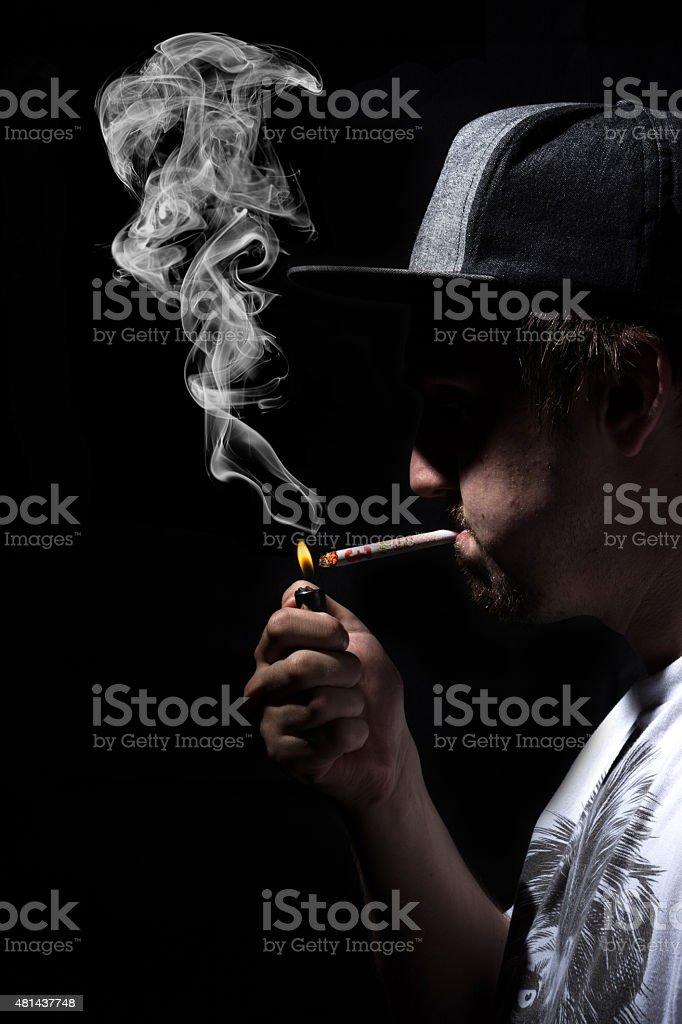 Man Smoking Rolled Up Bank Money Note Cigarette Wearing Cap. stock photo