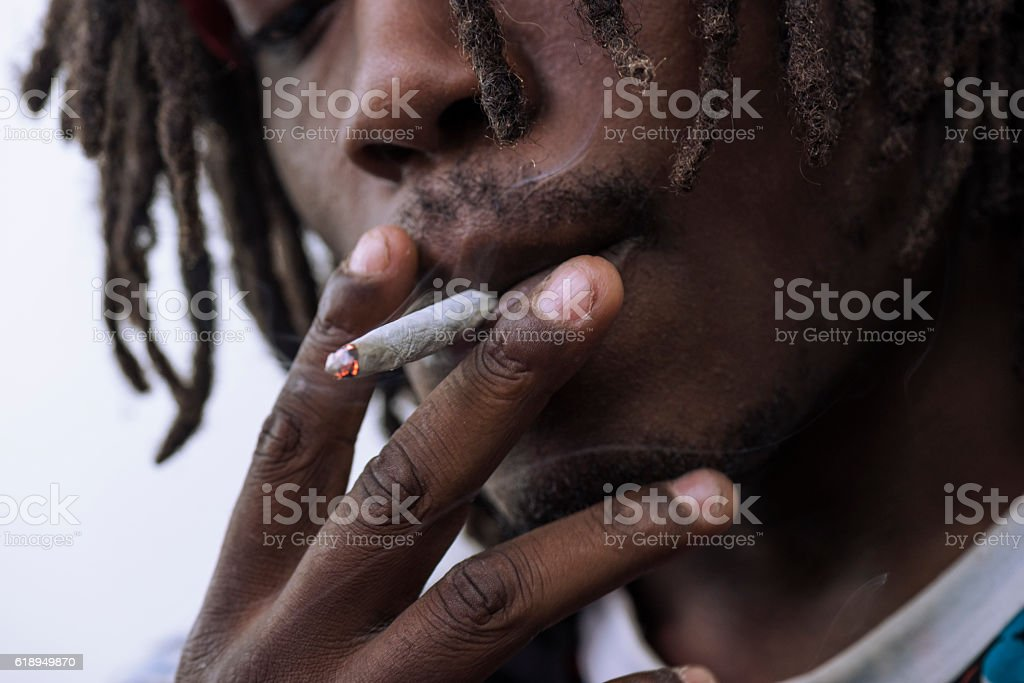 Man smoking white cigarette joint paper stock photo