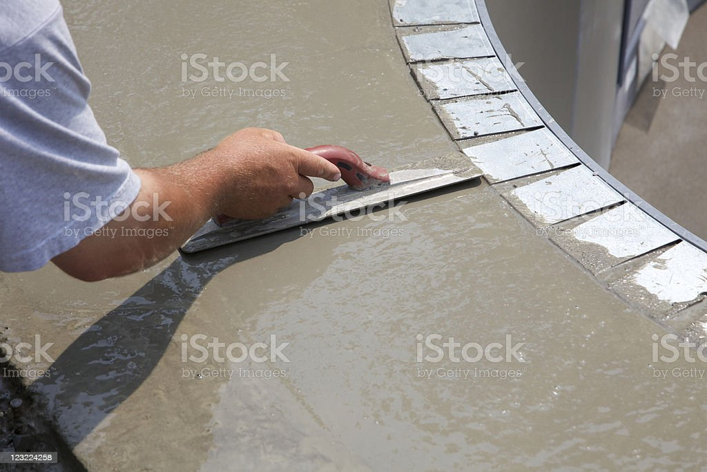 Man smoothing over wet cement in swimming pool construction stock photo