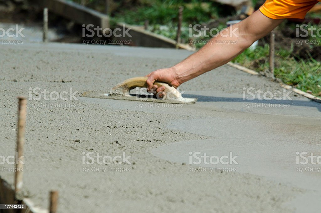 A man smoothing the wet concrete surface of a path stock photo