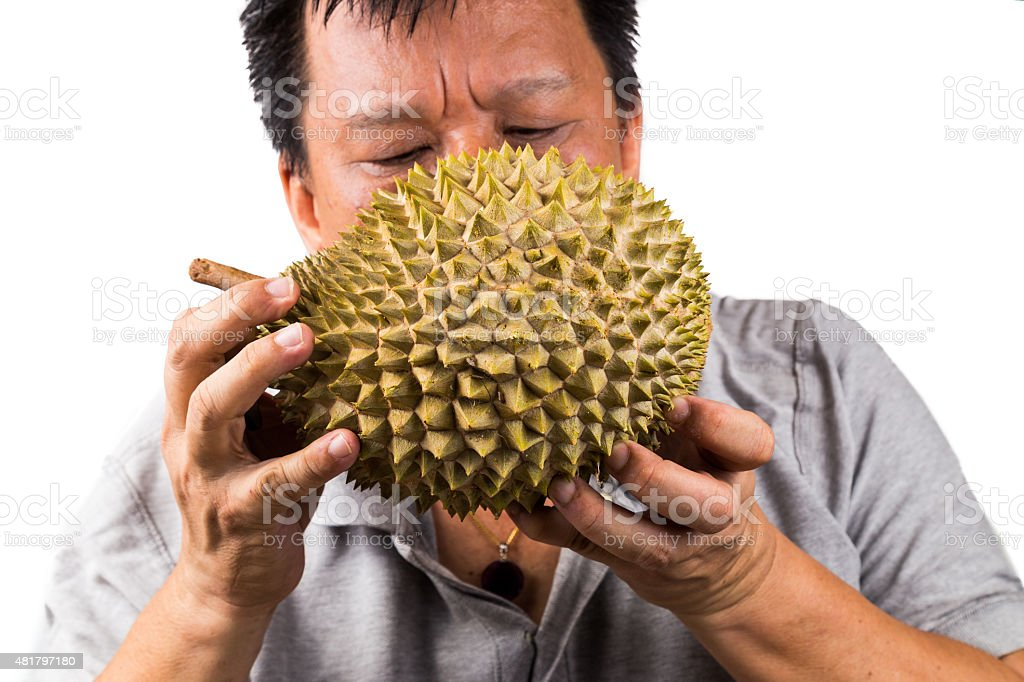 Man sniffing durian fruit to assess its quality and ripeness stock photo