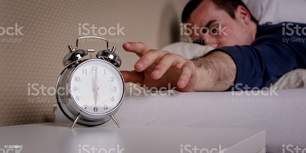Man snoozing alarm clock stock photo
