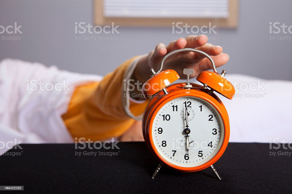 Man snoozing bright orange alarm clock stock photo
