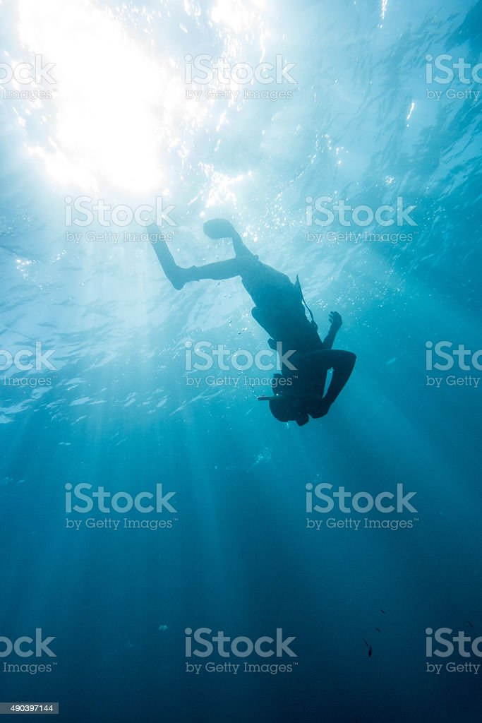 man snorkeling down deep sun reflection stock photo