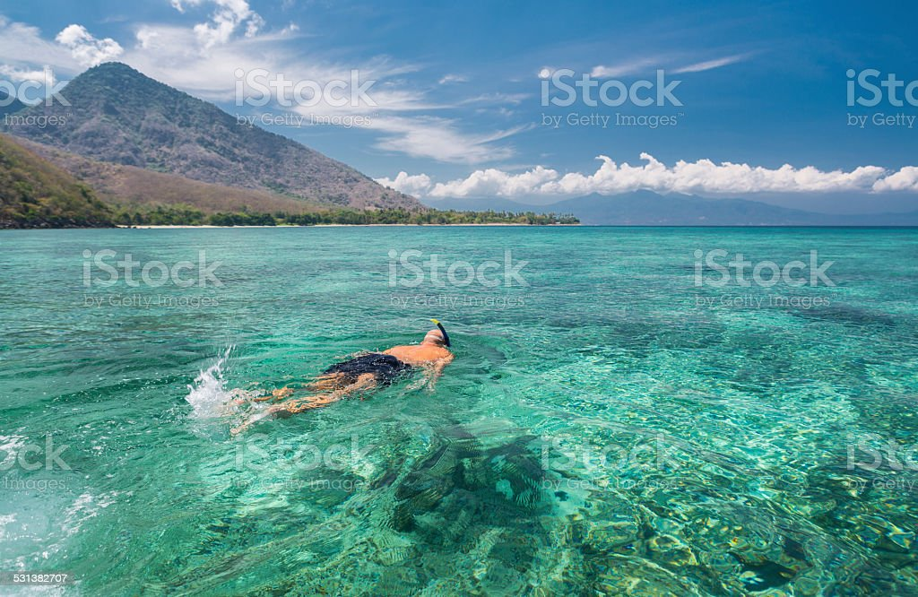 Man snorkeling in crystal blue waters stock photo