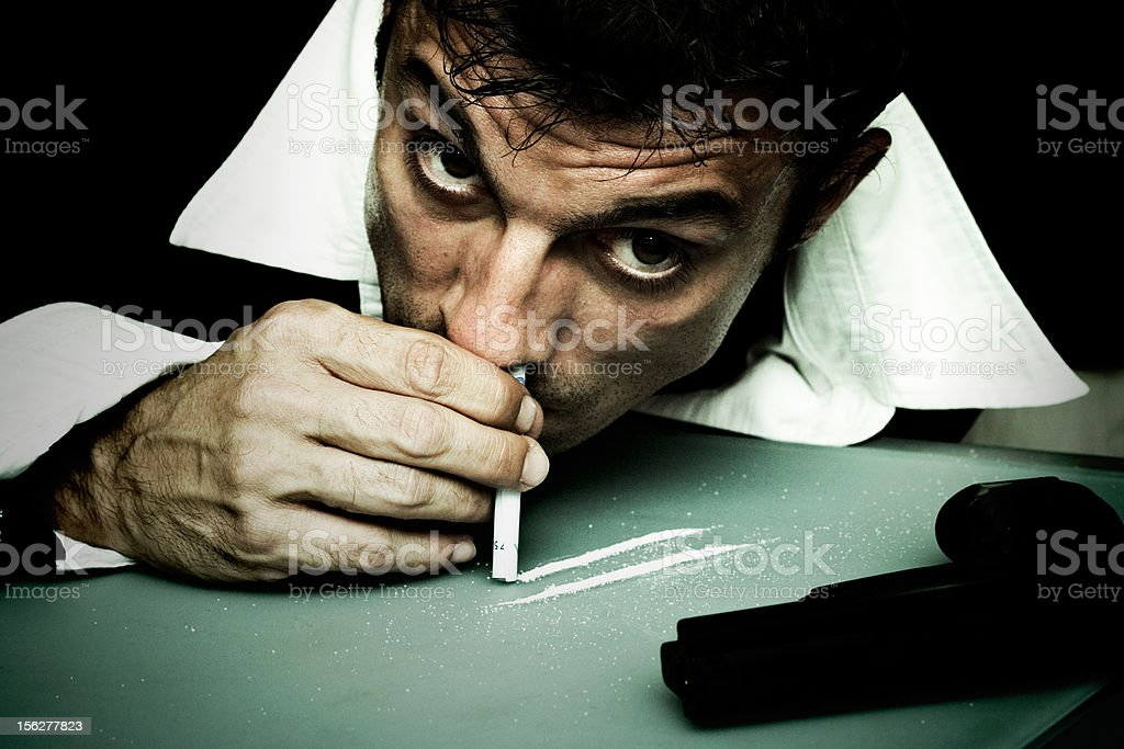 Man Snorting Cocaine Off Table royalty-free stock photo