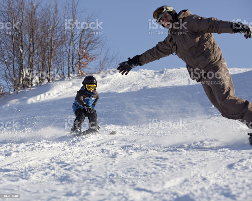 Man snowboarder and little skier stock photo