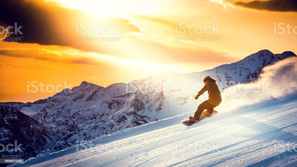 Man snowboarding at dusk stock photo