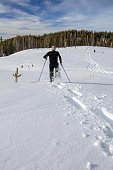 Man snowshoeing downhill in fresh snow