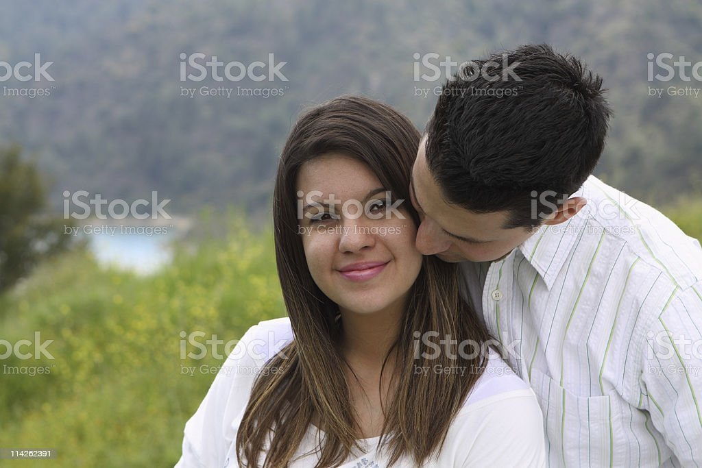 Man Snuggling and Kissing Attractive Woman royalty-free stock photo