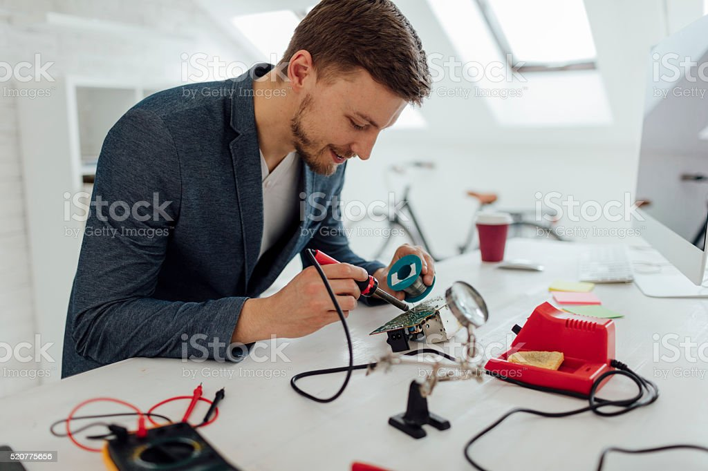 Man Soldering a circuit board in his office. stock photo