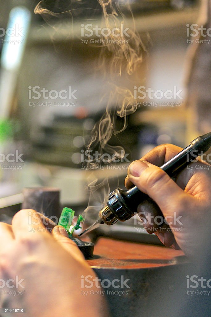 man soldering the ring by hands at jewelry workshop stock photo