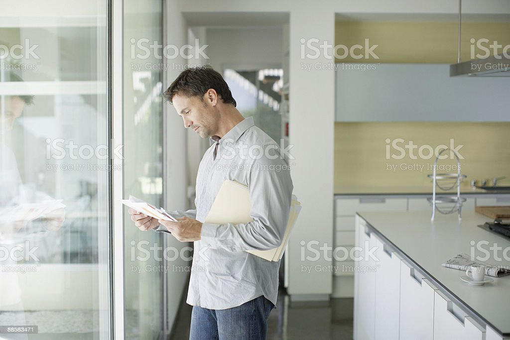 Man sorting mail at home stock photo