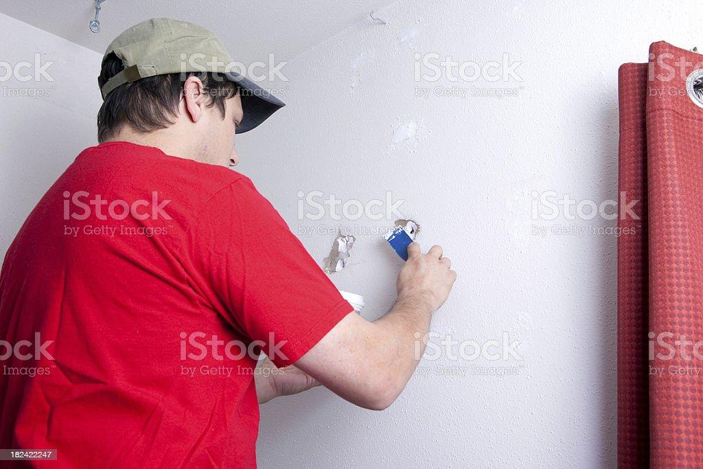 Man Spackling Wall stock photo