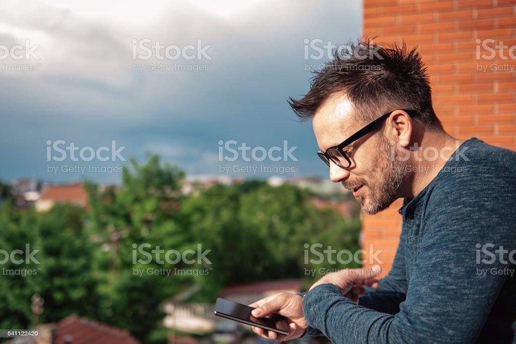 Man speaking into smart phone stock photo
