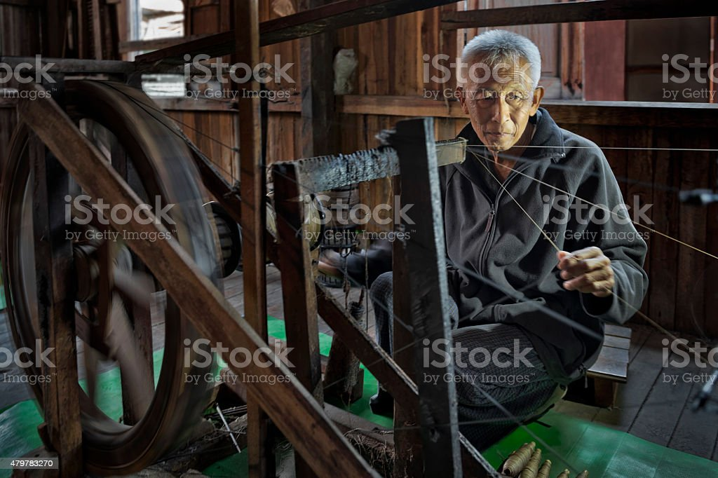 Man Spinning Lotus Fibre stock photo