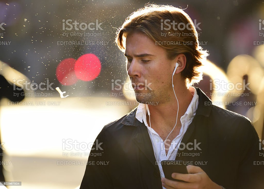 Man spitting and using mobile smart phone stock photo
