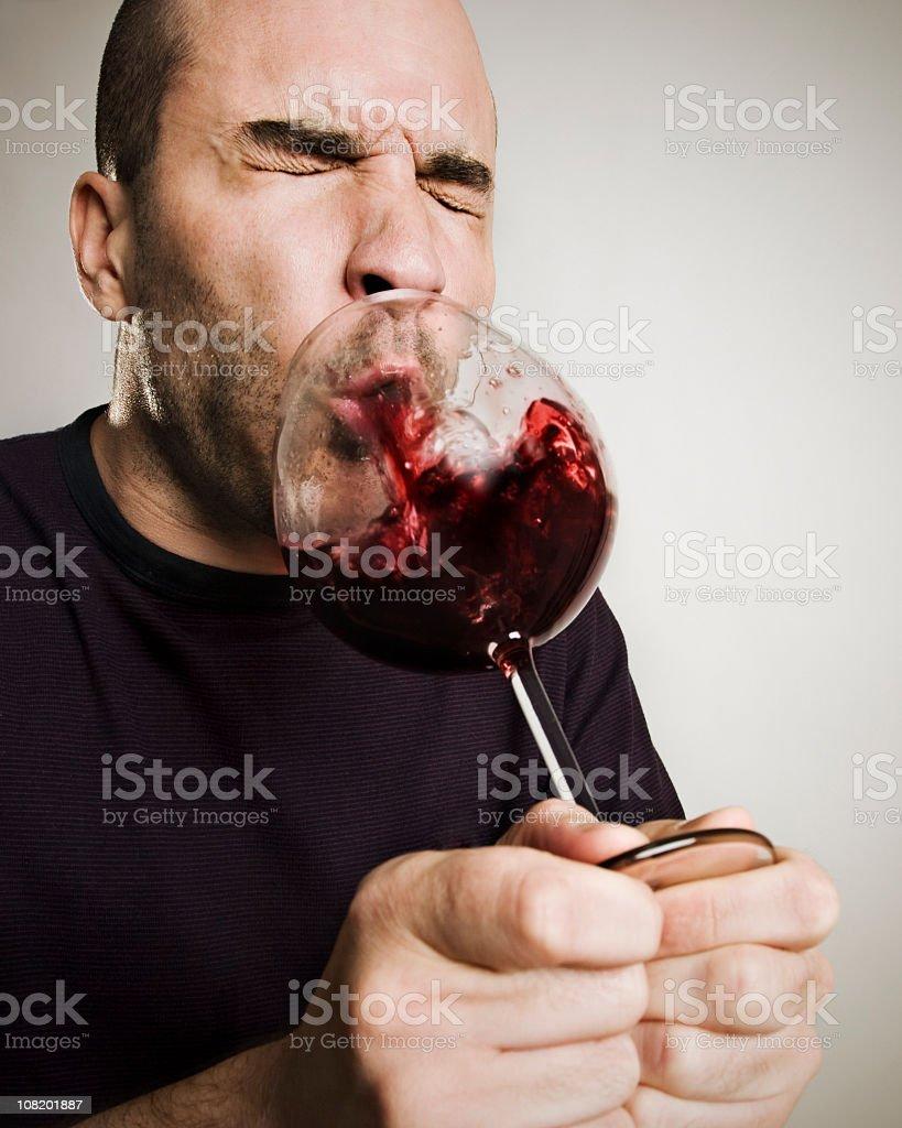 Man Spitting Wine Back into Glass stock photo
