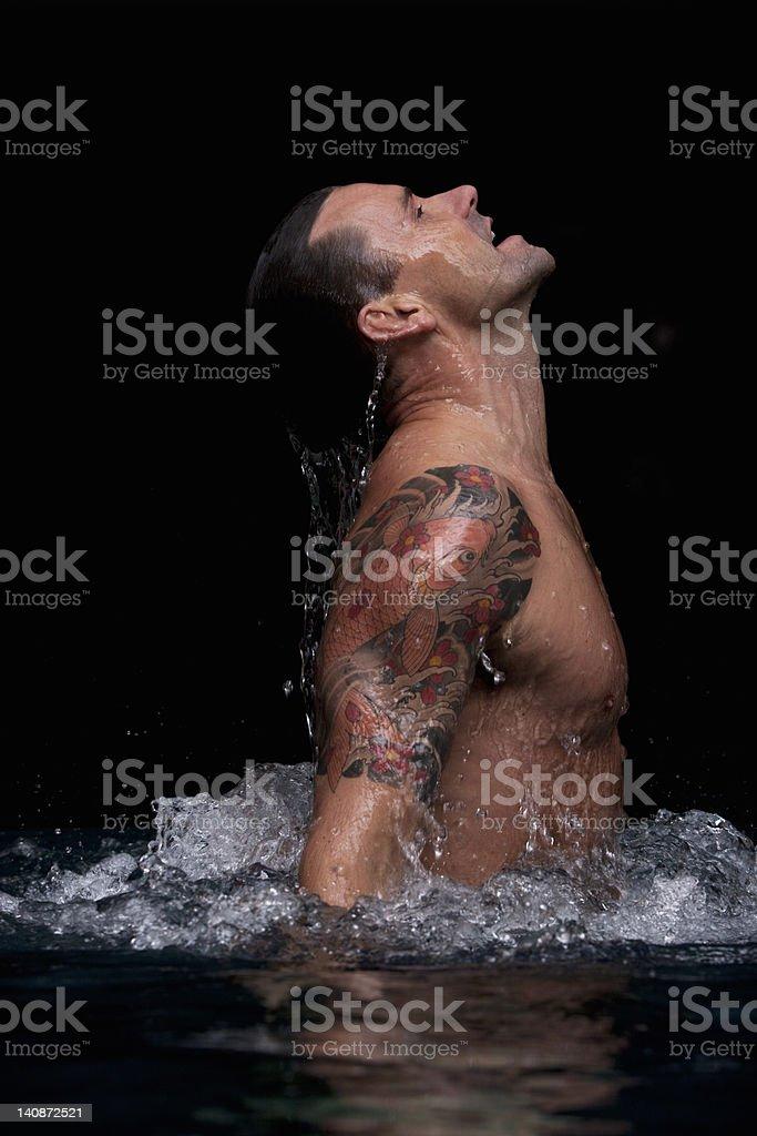 Man splashing in swimming pool stock photo