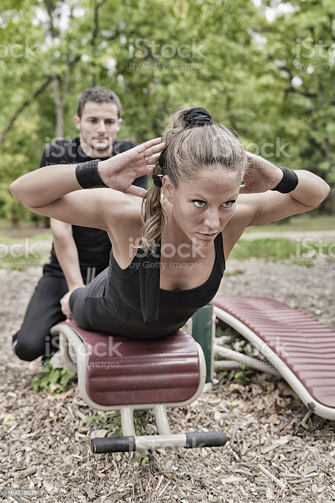 Man spotting a woman using fitness equipment outdoors stock photo