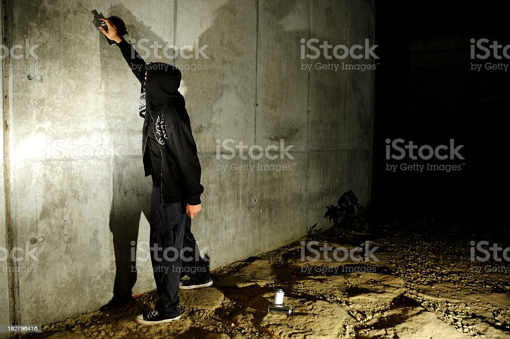 Man spray painting wall in the dark royalty-free stock photo