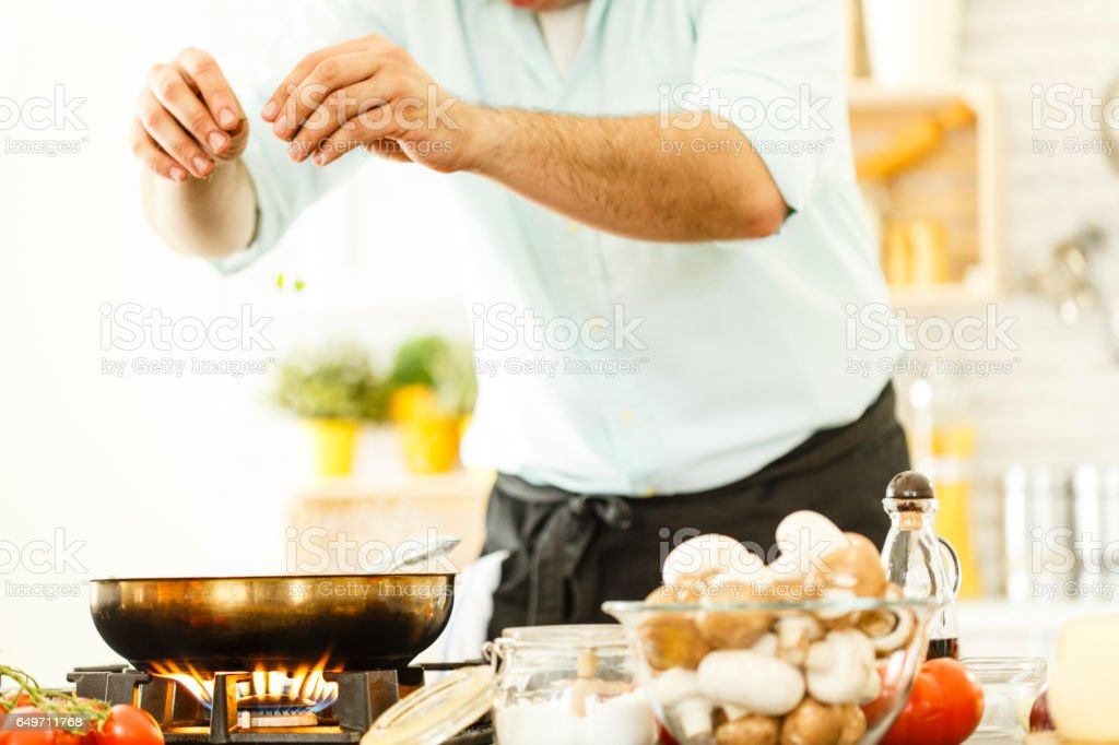 Man sprinkling seasoning, cooking dinner stock photo