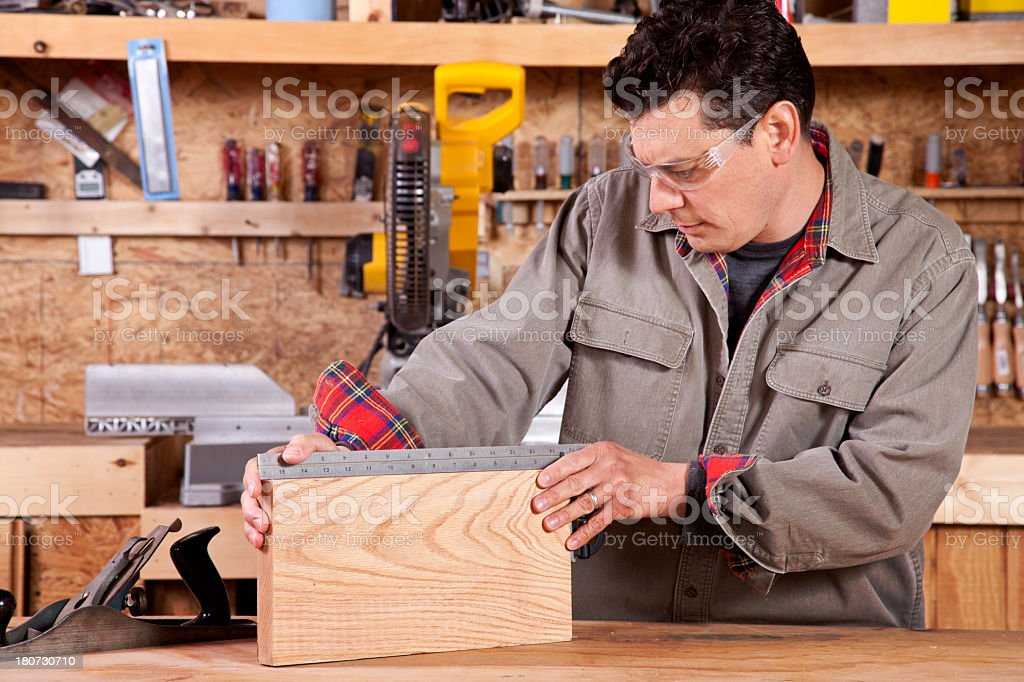 Man squaring wood with straight edge in wood shop royalty-free stock photo