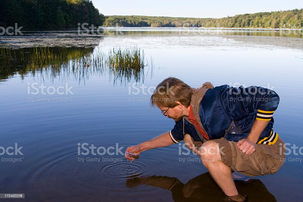 Man squatting collecting a sample from water stock photo