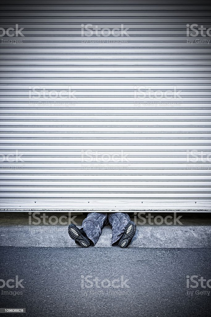 Man squeezed by roller shutter door stock photo