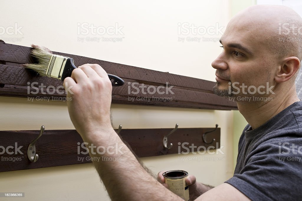 Man staining wood indoors using a paintbrush royalty-free stock photo