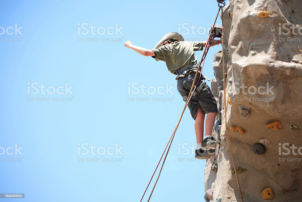 Man standing almost to the top of a rock climbing face stock photo