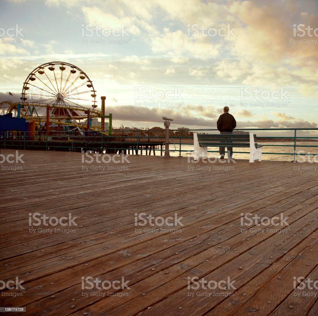 Man Standing Alone on Santa Monica Pier at Sunset royalty-free stock photo