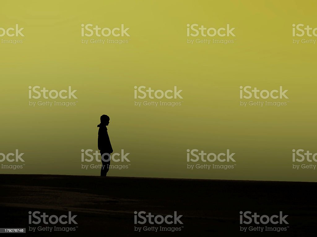 Man Standing Alone on the Beach with Green Sky royalty-free stock photo