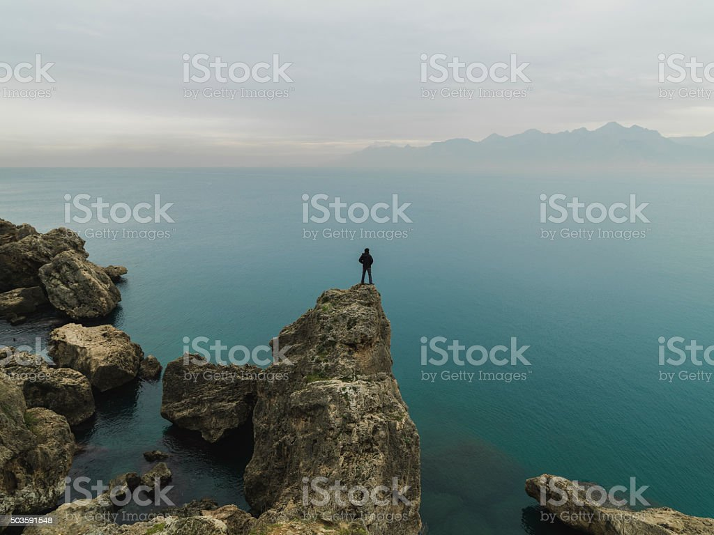 Man standing alone top of cliff and enjoying peaceful landscape stock photo