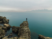 Man standing alone top of cliff and enjoying peaceful landscape