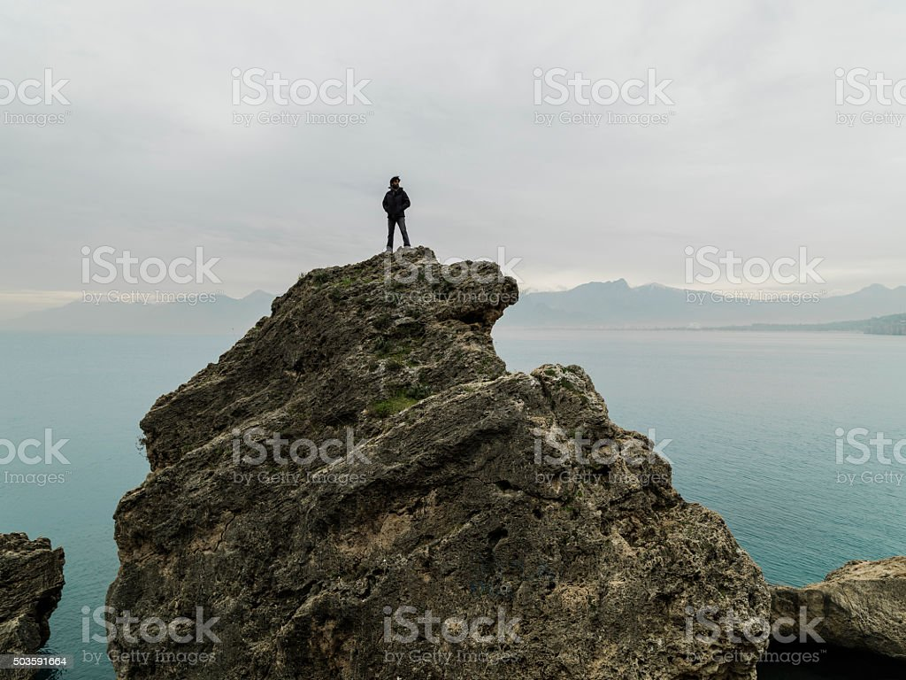 Man standing alone top of cliff stock photo