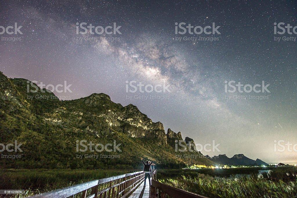 Man standing among milky way and mountain stock photo