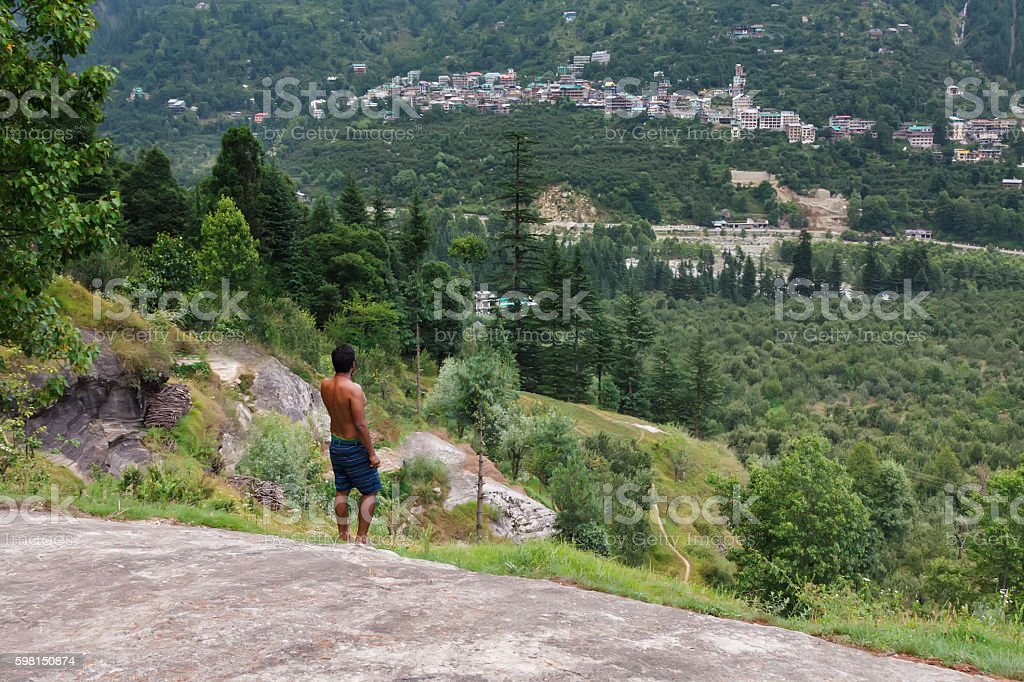 Man standing at a rock in green forest stock photo