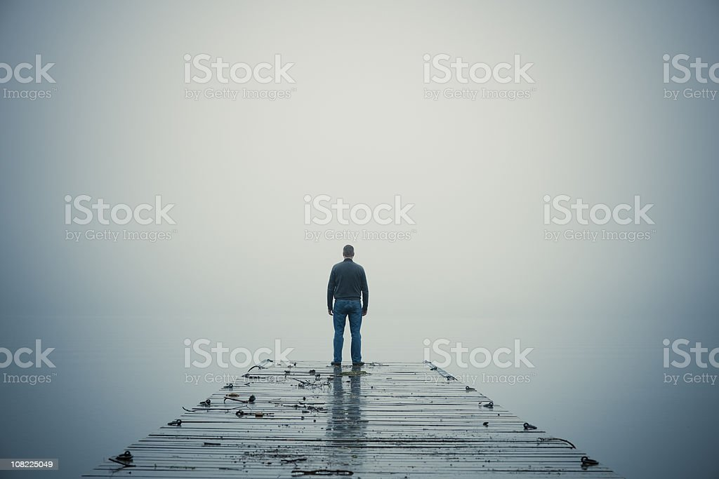 Man Standing at End of Dock During Foggy Day stock photo