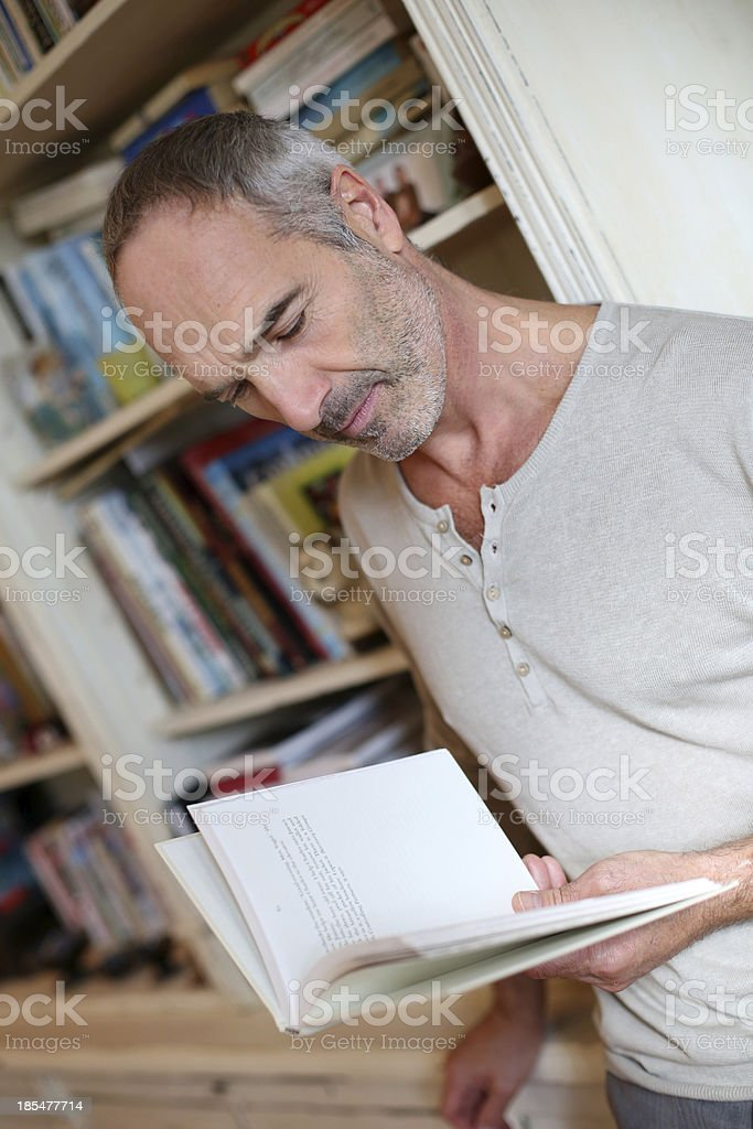 Man standing at home with book in hands royalty-free stock photo