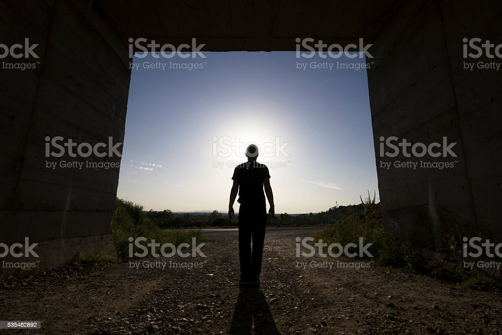 Man standing at large passage of concrete building, blocking sunlight stock photo