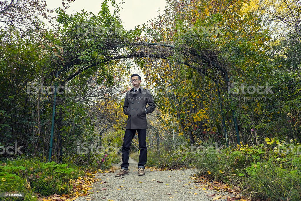 man standing at park with fall / autumn season colors stock photo
