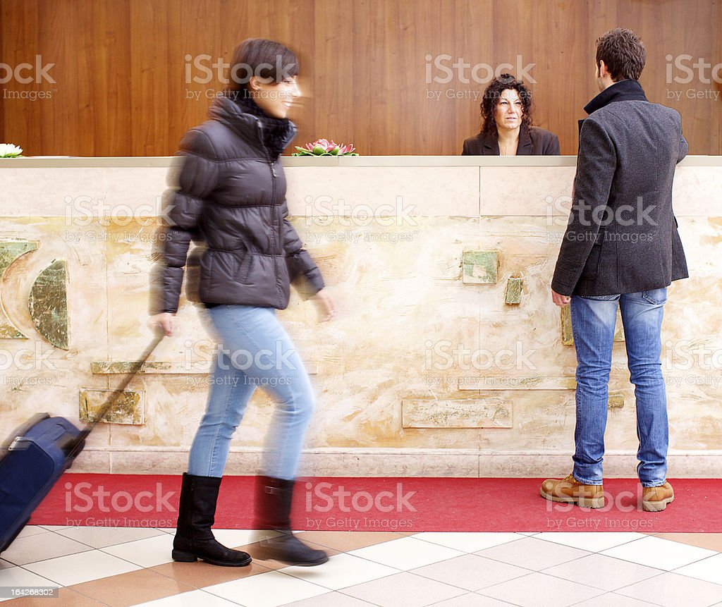 Man standing at reception desk in hotel lobby royalty-free stock photo