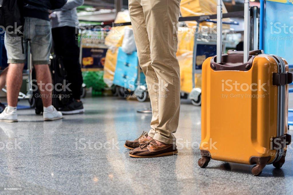 Man standing at terminal near luggage stock photo
