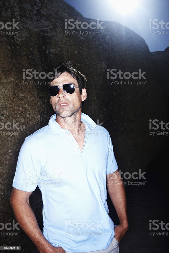 Man standing at the bottom of cliff royalty-free stock photo