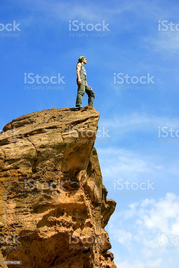 A man standing at the edge of a cliff on top of the world royalty-free stock photo
